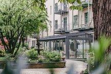 Außenbereich Rosengarten mit Wintergarten Innenhof Hotel München Maximilian Munich